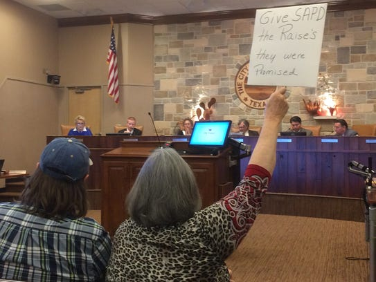 A San Angelo woman holds up a homemade sign in support