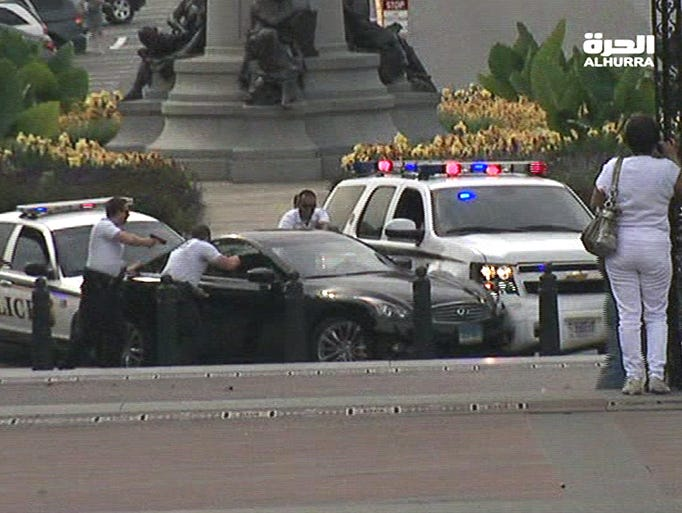 Police officers with guns drawn approach a black car near the U.S. Capitol. A volley of shots rang out outside the Capitol building as police intercepted a suspect, sending lawmakers and tourists scattering for cover and triggering a massive security operation.
