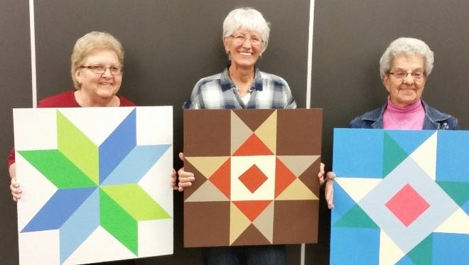 Betty Schloemer, Marilyn Brinkman and Delrose Fischer hold barn quilts painted at a Rocori Senior Center class.