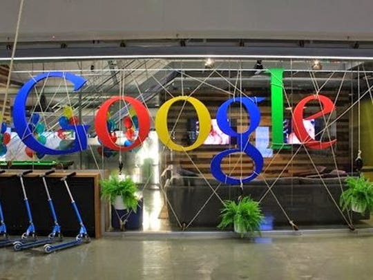 A Google sign suspended from indoor scaffolding.