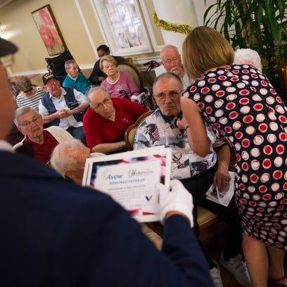 Ralph Benedict, a Navy veteran, receives a pin for