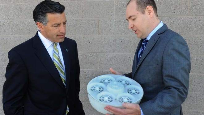 Republican Gov. Brian Sandoval, left, listens as Ashima Devices President and CEO Mark Richardson explains his company's drone product prior to the official announcement that Ashima Devices will be opening shop in Reno with an estimated 400 jobs.