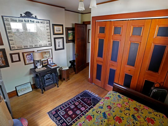 A bedroom on the first floor contains maps and photos from Bernard Zinck's travels and his home country, France. He painted the panels of the wooden doors to provide contrast.