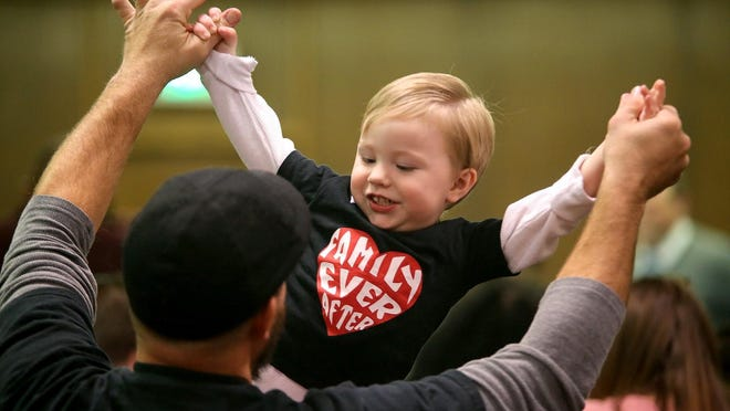Jairus Laughter plays with his son, Jude, during an adoption day celebration at the courthouse in 2018.
