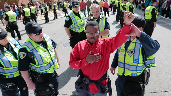 A man is asked by police officers to move from the street before being handcuffed during a protest in Madison on Wednesday. Dane County District Attorney Ismael Ozanne announced Tuesday that Madison police officer Matt Kenny would not face charges for the shooting death of unarmed Tony Robinson in March.