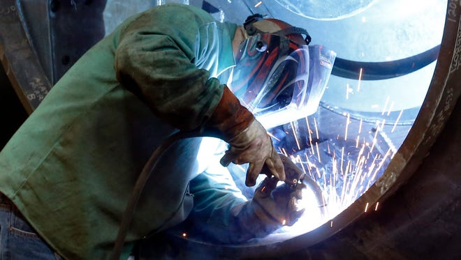 A man welds parts in fans for industrial ventilation systems at the Robinson Fans plant in Harmony, Pa.