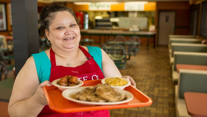 Angela Bishop, the owner of the new Angie's restuarant on West Broadway, holds a tray featuring her smothered porkchop dish with a side of candied yams and corn pudding. Aug. 1, 2017