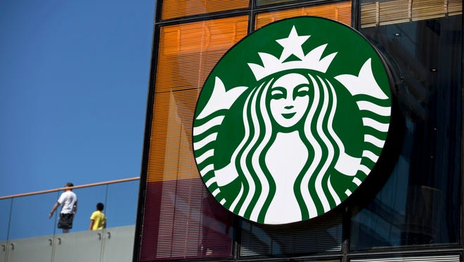 The Starbucks Corp. logo is displayed outside one of the company's coffee shops in the Sanlitun area of Beijing, China, on Monday, Sept. 8, 2014.