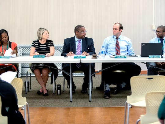 Lansing Housing Commission board president Tony Baltimore, center, executive director Martell Armstrong, far right, and board members, from left, Tamara Warren, Bethany Deschaine and Ryan Robinson hold a regular meeting on Wednesday, June 27, 2018, in the front office of the LaRoy Froh housing complex in Lansing. The Lansing Housing Commission, a public housing agency that manages more than 800 units throughout the city, has come under scrutiny after a June 7 fire killed Tarshrikia Beasley, 43, and her 5-year-old son Elijah Brown at a townhouse in the LaRoy Froh complex, which is owned and operated by the LHC.