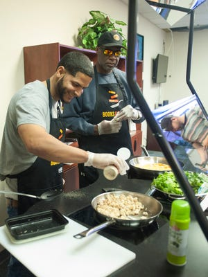 (From left) Jose Rodriguez and Turan C. Lee cook during a cooking/nutrition class in Camden with a new mobile kitchen, part of the Camden County Library System's newest initiative on food literacy.