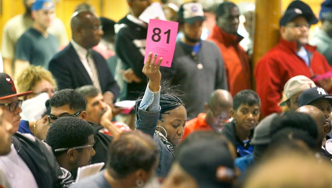 Esther Torres raises her bidding number during a tax foreclosure auction at the Edgerton Community Center. There were more than 800 properties up for auction.