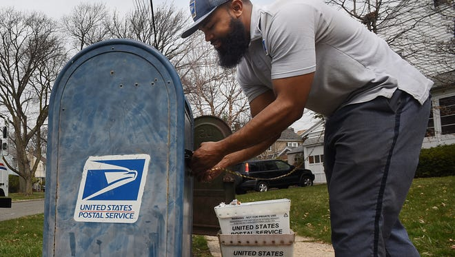 Jimmy Henry, a U.S. Postal Service letter carrier, empties a collection box at the intersection of Demarest Avenue and Lindbergh Boulevard in Bloomfield.