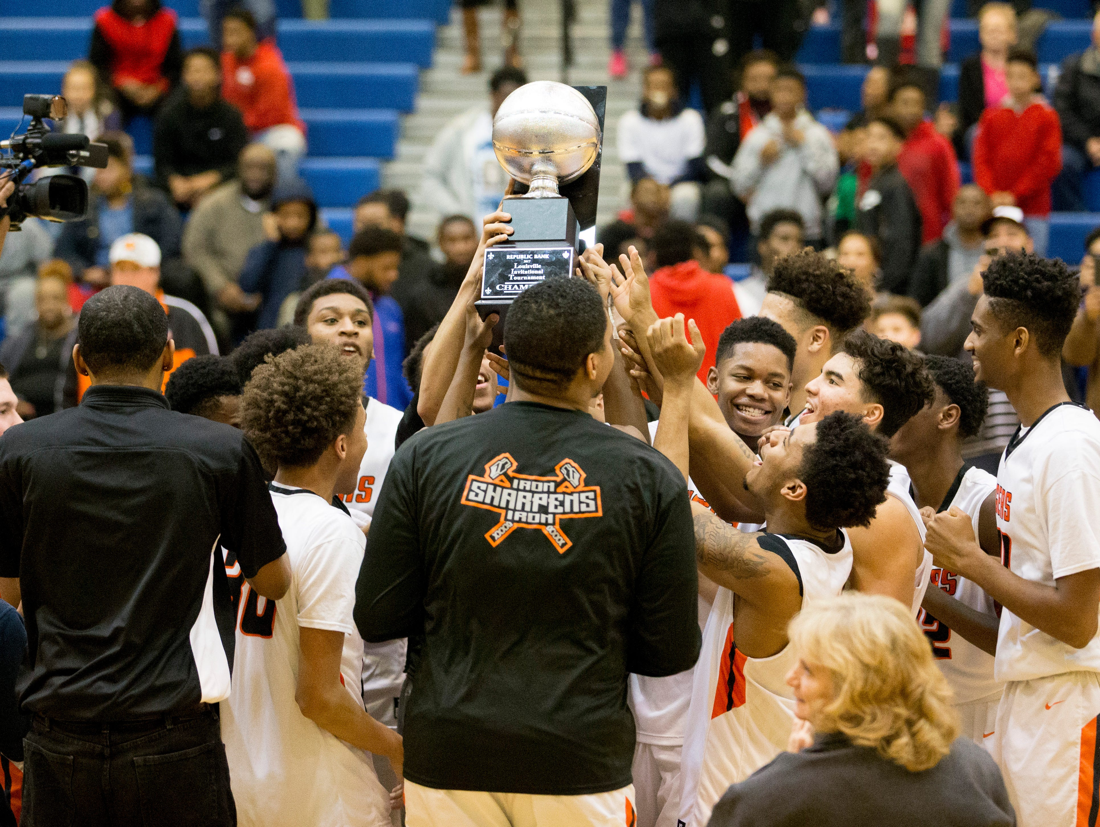 Members of the Fern Creek Tigers basketball team hoist the trophy after winning the championship game of the Louisville Invitational Tournament between the Fern Creek Tigers and the Trinity Shamrocks.