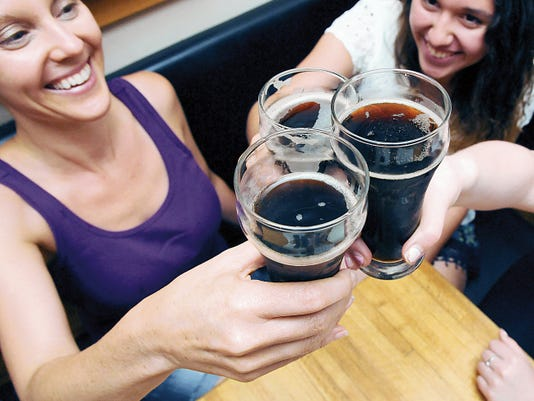 "April Sexton, left, Emma Sexton, right, and Noalani Mirsch (not pictured), of Eugene, Ore., raise and touch their glasses on Tuesday at High Desert Brewing. ""We are from out of town and came specifically for the root beer and nachos,"" said Sexton."