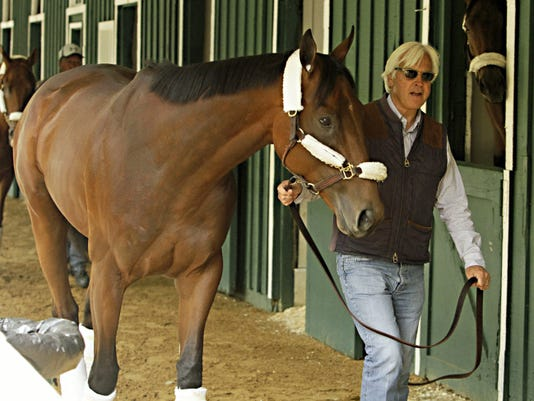 Kentucky Derby winner American Pharoah is held by trainer Bob Baffert at the stakes barn at Pimlico Race Course in Baltimore on Wednesday. The Preakness Stakes horse race is Saturday.