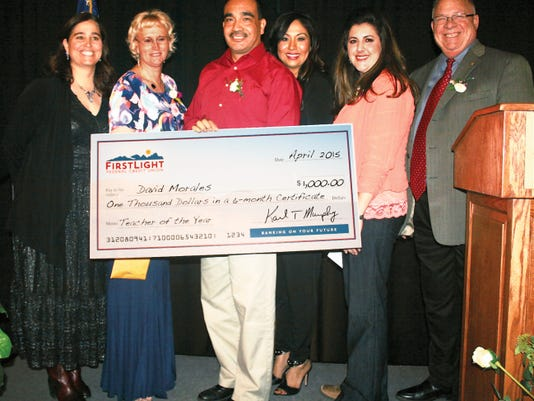Mayfield teacher David Morales holds his 1,000 cash award from Firstlight Federal Credit Union after being selected as the LCPS Teacher of the Year. Those with him are, left to right,  Dr. Thea Hand, coordinator of LCPS professional development; Lonna Andrews, third runner-up, Mesa Middle School; Laura Bryant, second runner-up, Central Elementary; Rachel Knight, first  runner-up, Centennial High; and Superintendent Stan Rounds.