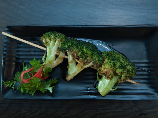 A focus on Japanese street foods means at Rayaki there's an entire menu of robatayaki, barbecued skewers that you order by the each, penciling in whatever quantity your heart desires on a paper menu. Here is a broccoli skewer is shown.