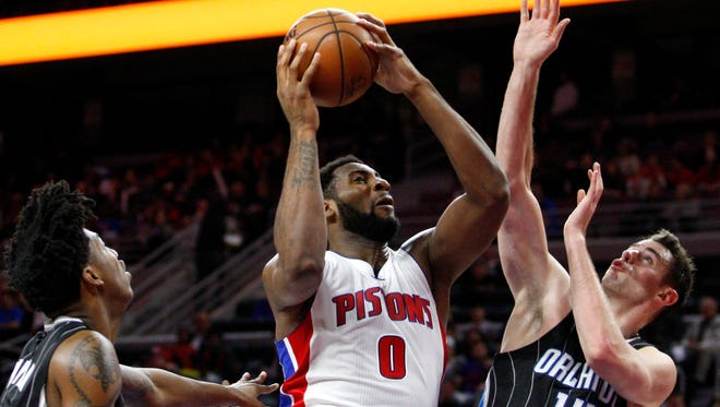 Pistons center Andre Drummond (0) grabs the loose ball in front of Magic guard Elfrid Payton, left, and forward Jason Smith during the fourth quarter of the Pistons' 118-102 win Wednesday at the Palace.