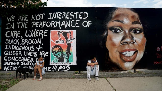 Kassiday Fonte-Anderson, left, with her dog Moose, and her brother Kam'ryn Fonte sit in front of a painting of Breonna Taylor, killed by Louisville police in her home in March, that they were helping to display along Fountain Street in Providence on Tuesday.