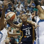 Indiana Fever's Briann January, center, attempts a layup between Minnesota Lynx's Rebekkah Brunson, left, and Maya Moore, right, in the first half of Game 1 of the WNBA basketball finals Sunday in Minneapolis.
