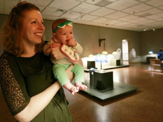 Erin Mattila and her 4-month-old daughter Isabelle look on a Tiffany Glass lamp during an exhibition at Leigh Yawkey Woodson Art Museum in Wausau.