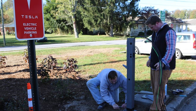 Workers install Tesla High-Speed High-Power Wall Connector and standard J1772 unit at Brevard College.