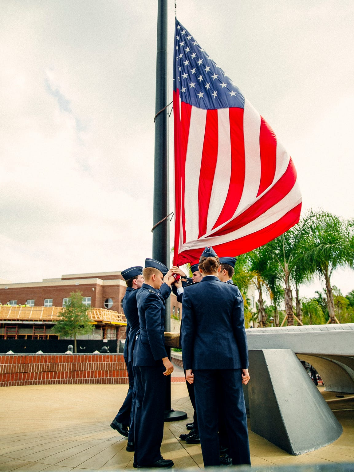 Members of UCF's ROTC raise the flag on campus.