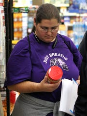 "Cathy Hawk, of Coshocton, examines the nutritional facts on a jar of peanut butter Oct. 23 at Baker's IGA in the Downtowner Plaza during ""Take Charge of Diabetes,"" a free six-week program hosted by Coshocton Hospital."