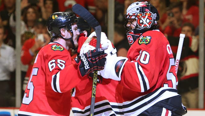 Chicago Blackhawks center Andrew Shaw (65) and goalie Corey Crawford (50) celebrate after beating the Anaheim Ducks 5-2 in game six of the Western Conference Final of the 2015 Stanley Cup Playoffs at United Center.