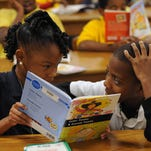 Lillie Burney Elementary students Talyiah Wiley and Clide Mitchell read a book in the library. Mississippi's Literacy-based Promotion Act requires third-grade students to show they can read at or above grade level to move on to fourth grade.