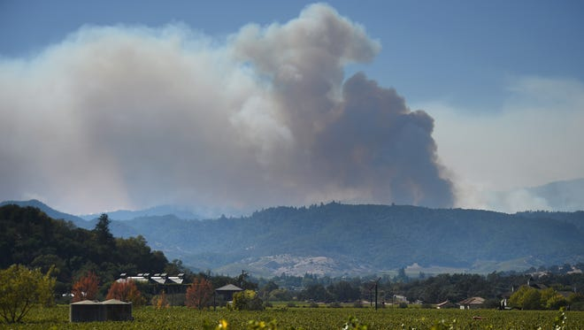 A wildfire burns in the mountains to the west of Napa Valley, Calif., on Oct. 12, 2017.
