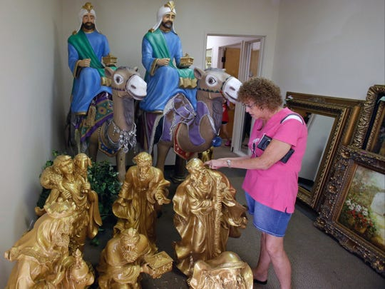A shopper looks over the some of the many items available at an estate sale from The Holy Land Experience religious theme park, Thursday, July 21, 2016, in Orlando, Fla. The Christian theme park is holding the sale amid declining revenue and contributions. The sale starts Thursday and lasts through Saturday. (AP Photo/John Raoux)