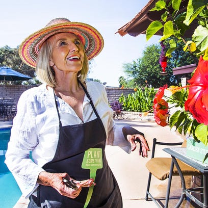 Jan Brewer waters the plants in her backyard Tuesday,