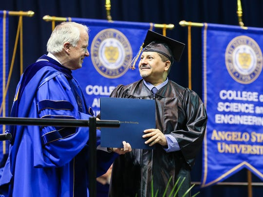 Joe Garcia shakes hands with Angelo State University President Brian May during the commencement ceremony Saturday, Dec. 16, 2017, at Junell Center.