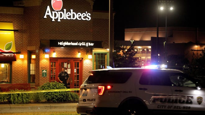 A police offer stands posted at the entrance of an Applebee's restaurant on Monday in St. John, a suburb of St. Louis, after a gunman opened fire inside the business killing one and injuring at least two other people inside.