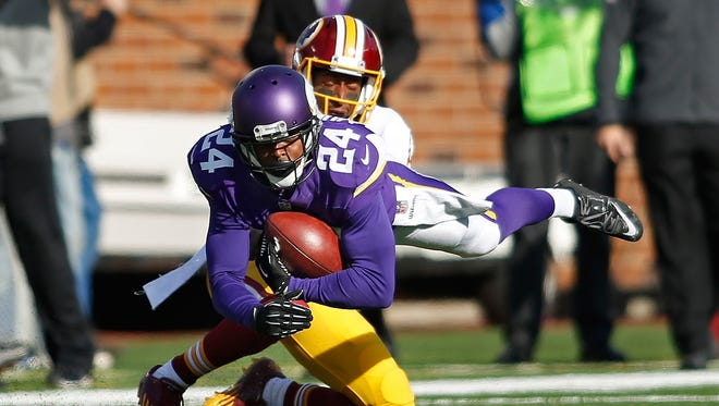 Minnesota Vikings cornerback Captain Munnerlyn (24) intercepts a pass intended for Washington Redskins wide receiver Andre Roberts (12) in the second quarter at TCF Bank Stadium.