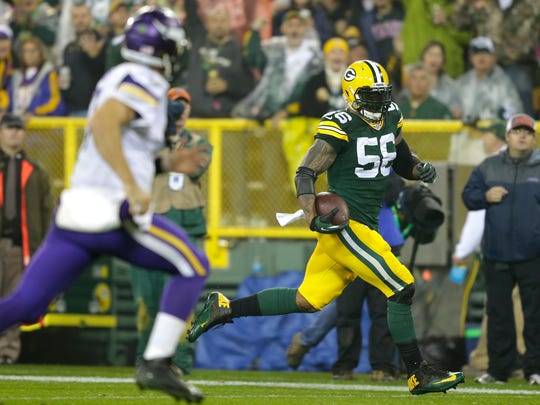 Green Bay Packers outside linebacker Julius Peppers runs back an interception for a touchdown against Minnesota Vikings quarterback Christian Ponder in the second quarter.