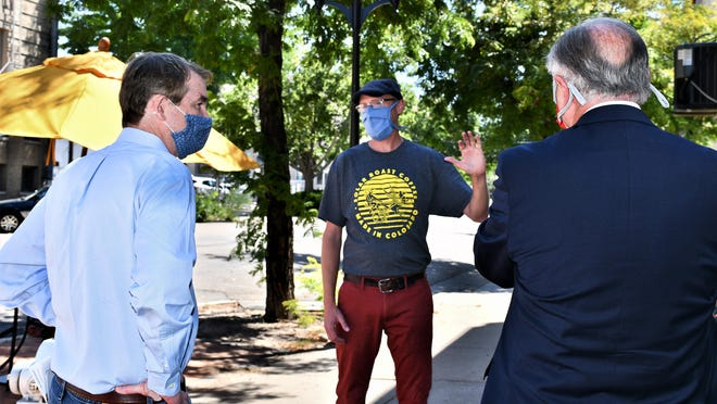 U.S. Sen. Michael Bennet, left, and Mayor Nick Gradisar, right, visit with Solar Roast Coffee owner Mike Hartkop Friday.