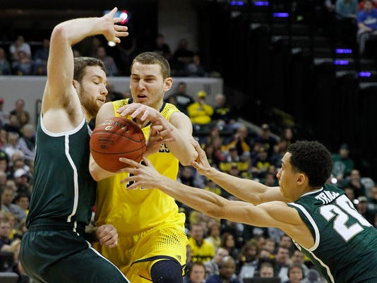 Michigan guard Nik Stauskas, center, loses control of the ball as he is defended by Michigan State forward Matt Costello, left, and guard Travis Trice in the first half of an NCAA college basketball game in the championship of the Big Ten Conference tournament on Sunday, March 16, 2014, in Indianapolis. (AP Photo/Kiichiro Sato)