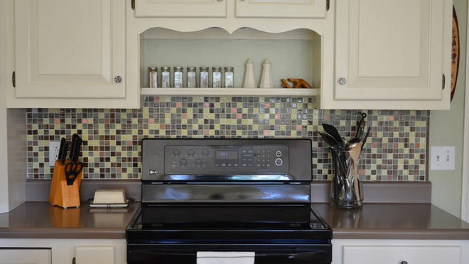 This backsplash is comprised of small glass and copper tiles which came in predesigned sheets that were easily stuck to the walls using peel-and-stick tile adhesive.