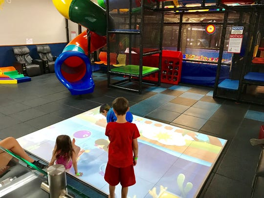 Kids play with an interactive floor game that is part