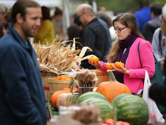 Areta Zhulla of Indianapolis sizes up some mini pumpkins from the VanAntwerp's Farm Market stand during the afternoon Farmer's Market on Market Street in downtown Indianapolis on Wednesday, September 17, 2014.