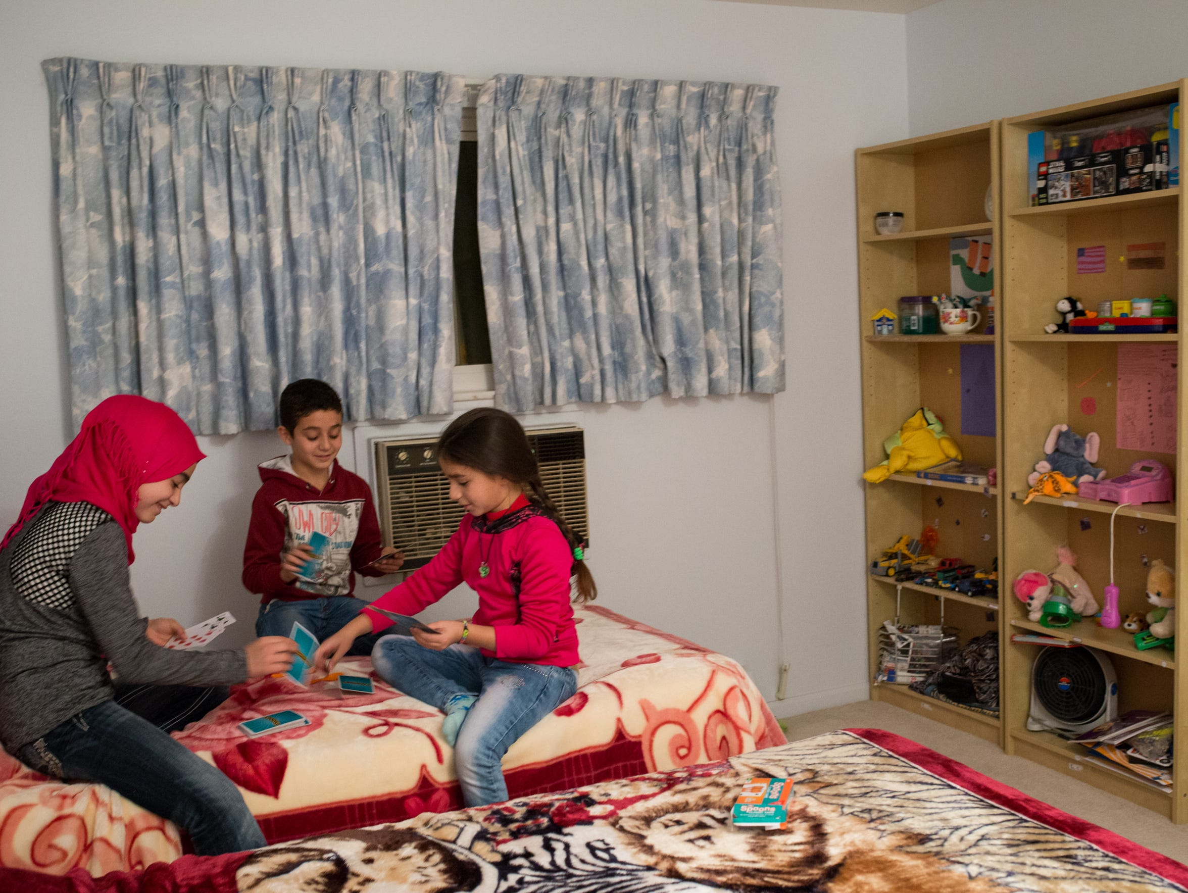 From left, Esraa Sharaf, 12, plays a card game with