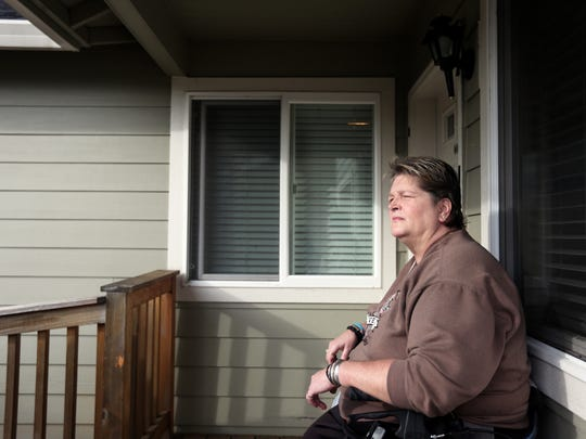 Holly Schmitz sits on the porch of the adult foster care home she has lived for six months, but which she will have to move out of by Monday, Feb. 1, 2016. Schmitz will be moving to Silverton, but she said she hopes to return to this house eventually.