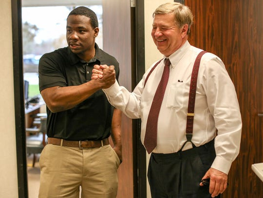 Omar Pouncy, 28, grasps hands with his lawyer David