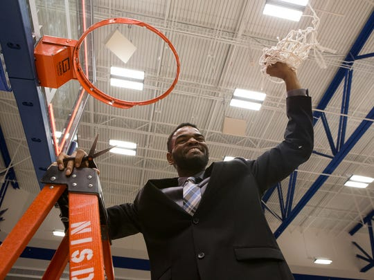 Veterans Memorial head coach Xzavier Gaines holds up the game net after defeating Dripping Springs 58-42 in the Region IV-5A final at Northside Sports Gym in San Antonio  on Saturday, March 4, 2017.