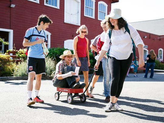 Participants pull volunteer Susanne Ransen in a wagon