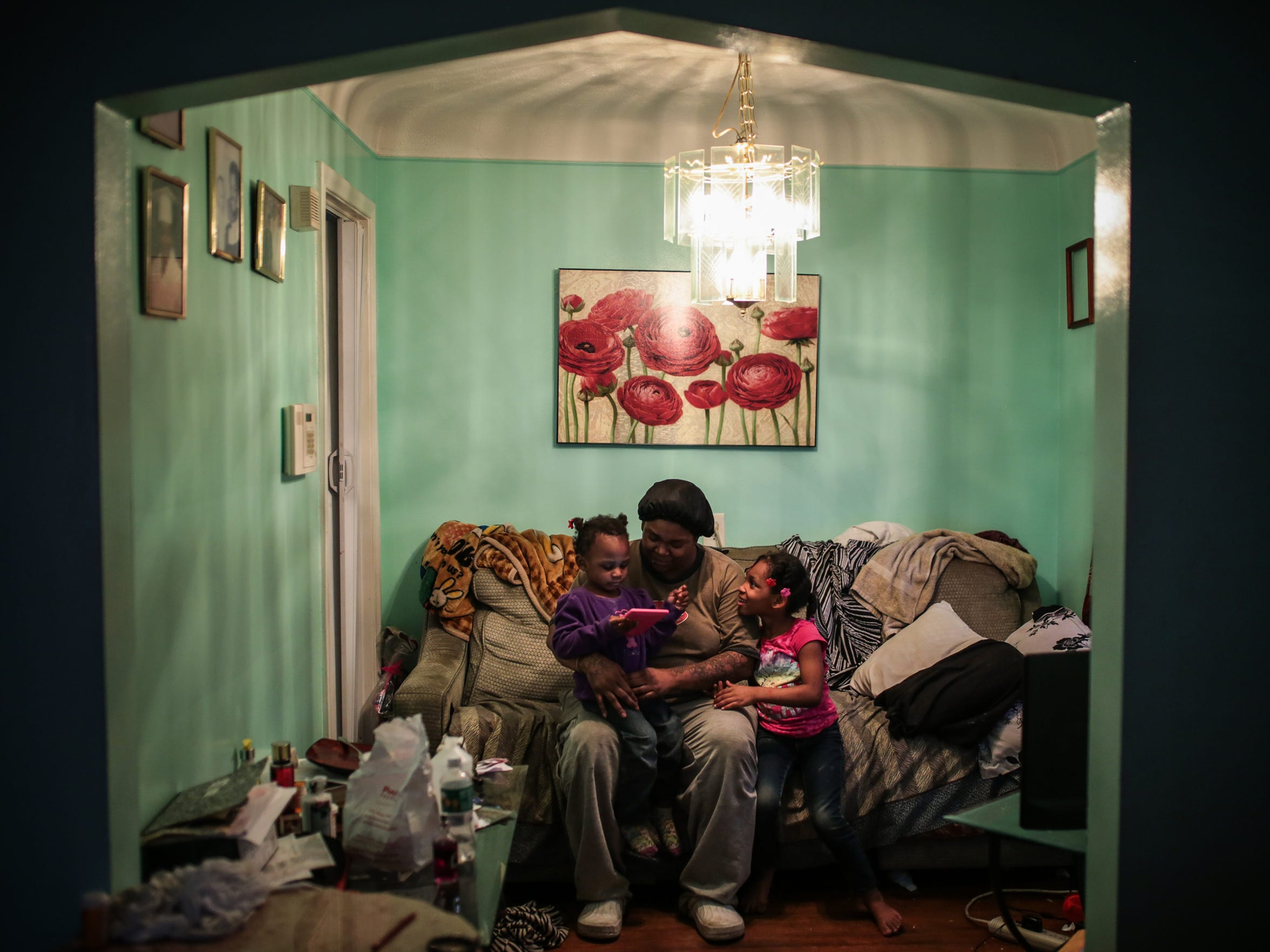 "Tatiana Young, 29, of Detroit, sits in a living room alcove with her two daughters, Miyako Young, 5, right, and Malaysia Foley, 2, on March 7, 2017. Tatiana shares the home with her four children, an elderly mother, an elderly aunt and an older cousin. Although they live in what is statistically one of Detroit's most dangerous neighborhoods, Tatiana said her block is relatively safe. ""The neighborhood is not that bad,""she said."