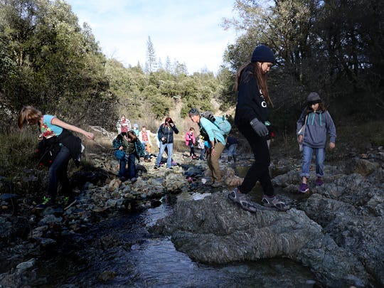 Kathy Hill, a field instructor at Whiskeytown Environmental School, center, leads a group of fifth-graders on a hike in February 2018.