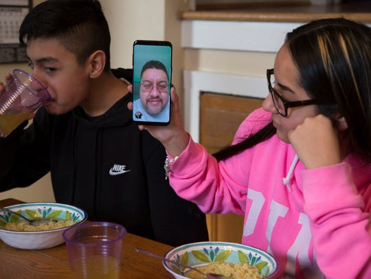 Jorge Garcia, 12, left, sips some Mt. Dew in his grandmother's Lincoln Park kitchen on Friday, Jan. 19, 2018 as his sister Soleil, 15, holds the phone up after reaching their dad Jorge Garcia, 39, who was deported on Jan. 15, 2018.